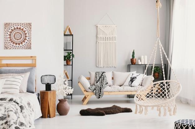 壁にマクラメが付いた明るいリビングルームのインテリア、枕と毛布が付いたベージュのソファ、ハンモックチェア、ふわふわのラグ、実際の写真のベッドのそばに立っているランプ付きのベッドサイドテーブル