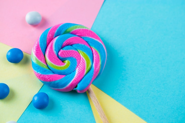 Bright lollipop candy on colorful background, flat lay shot