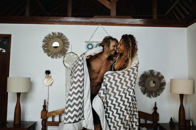 Ragazzo e ragazza amanti luminosi in un ambiente romantico sono coperti con una calda coperta a righe