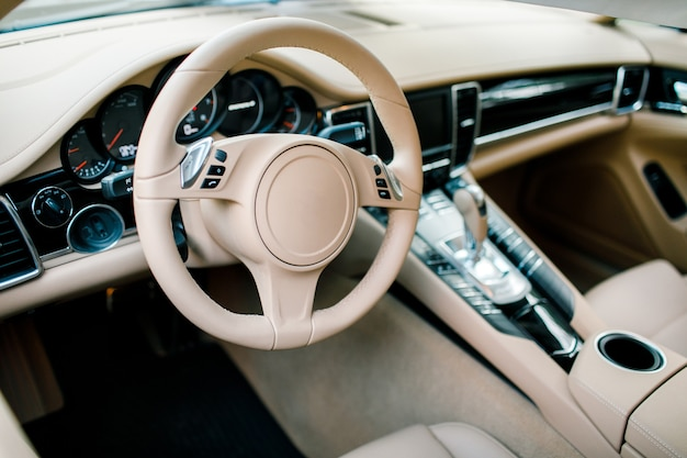 Bright luxury interior of the car-steering wheel, gear lever and dashboard.