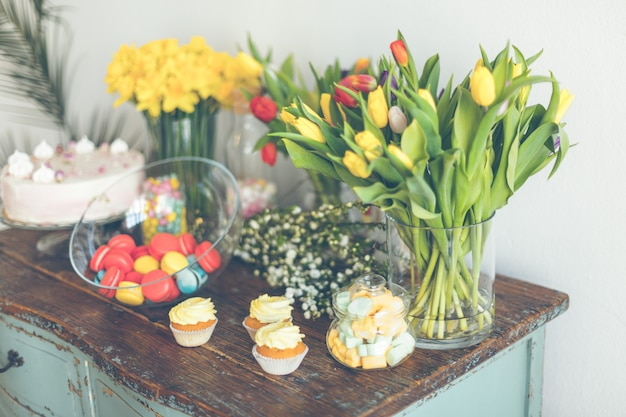 Bright macarons and cupcakes on a wooden table with flowers