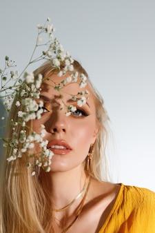 モデルの前の明るいメイク。顔は花で覆われています。ファッション写真
