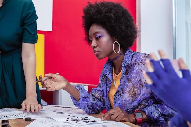 明るいメイク。明るい化粧を剃る巨大なイヤリングを身に着けているスタイリッシュなアフリカ系アメリカ人の学生