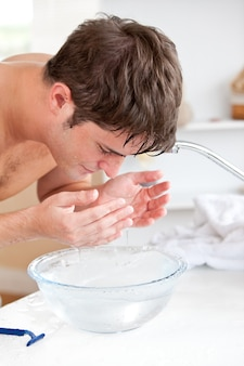 Bright man spraying water on his face after shaving in the bathroom