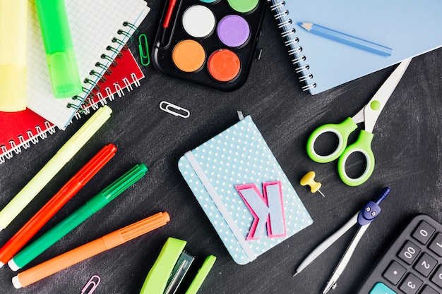 Bright messy stationery and notebooks on grey background