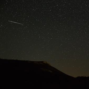 山の斜面の上の明るい流星
