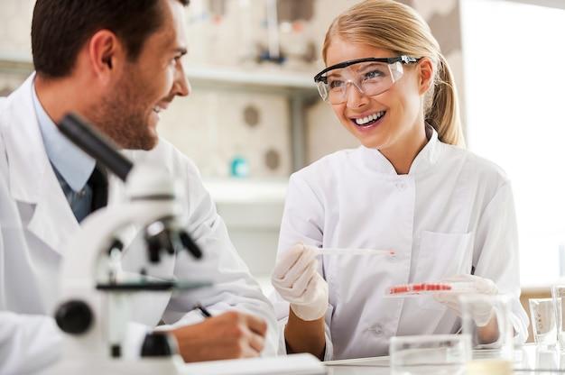 직장에서 밝은 마음. 두 명의 쾌활한 젊은 과학자들이 실험을 하고 실험실에 앉아 있는 동안 서로를 바라보고 있다