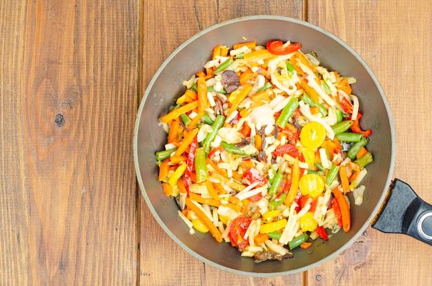 Яркий микс тушеных овощей на сковороде на деревянном