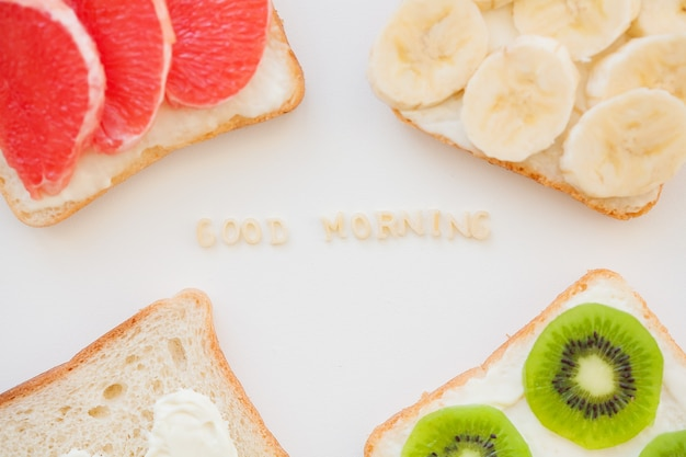 Bright mix of sandwiches for breakfast fruit, vegetables, fish inscription good morning