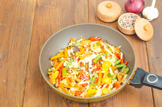 Bright mix of stewed vegetables in frying pan on wooden table