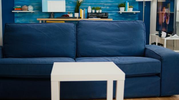 青い家具と壁があり、美しく装飾された、誰もいない明るくモダンなリビングルーム。バックグラウンドでテレビと居心地の良いアパートの非常にシンプルでモダンな装飾