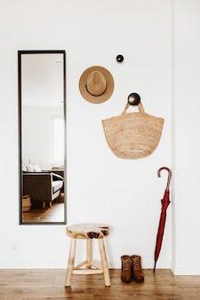 明るくモダンなスカンジナビアのインテリアデザイン。鏡、スツール、帽子、ストローバッグ、傘、靴のあるリビングルーム。