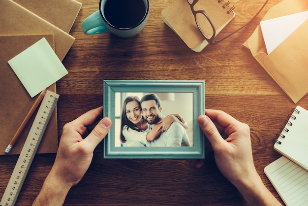 Bright moments together. close-up top view of man holding photograph of young couple over wooden desk with different chancellery stuff laying around