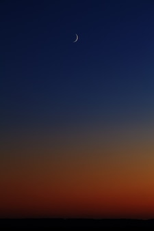 日没後の夕方の空の明るい月。