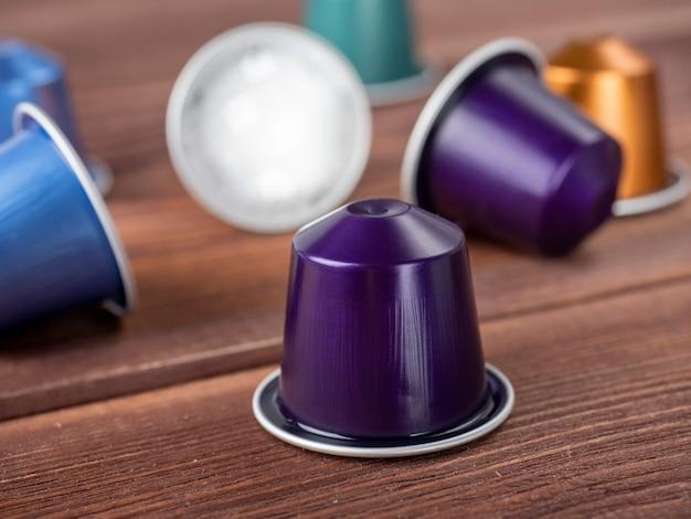 茶色の木製の背景にコーヒーと明るいマルチカラーカプセル。クローズアップ、側面図