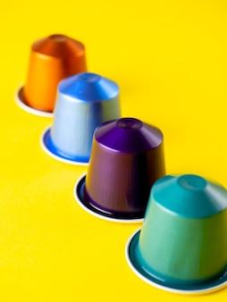 黄色の背景にコーヒーマシン用の明るいマルチカラーのコーヒーカプセル。側面図、セレクティブフォーカス