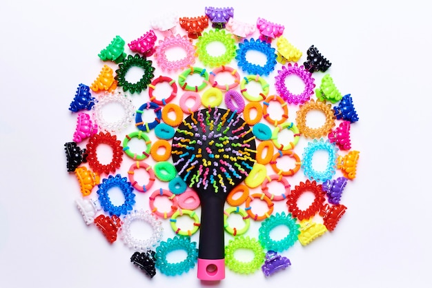 Bright multi colored comb in a circle of small colorful hairpins and rubber bands for hair