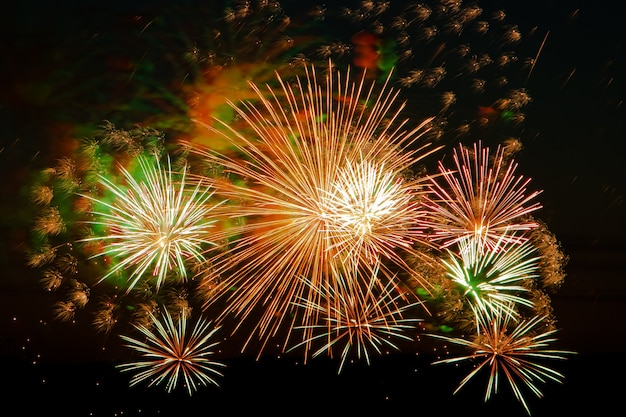 Bright multi-colored fireworks on a festive night. beautiful color flashes in the dark sky for a holiday.