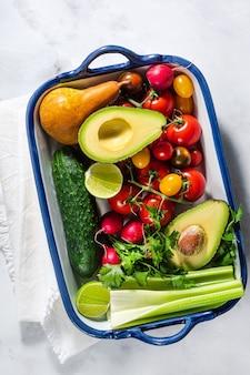 明るいマルチカラーの新鮮な夏野菜と天板のテーブルの上の果物。料理、サラダの材料