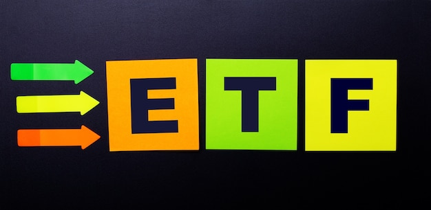 Bright multi-colored paper stickers on a black background with the text etf exchange traded funds
