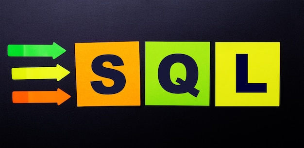 Bright multi-colored paper stickers on a black surface with the text sql