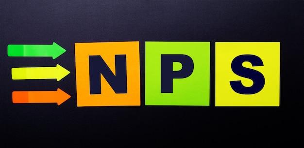 Nps net promoter score 텍스트가있는 검정색 배경에 밝은 멀티 컬러 종이 스티커