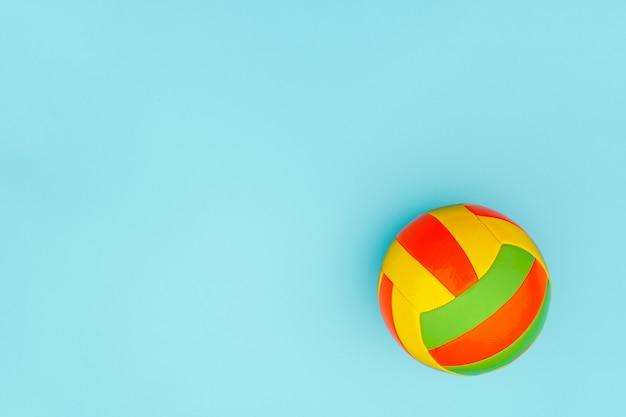 Bright multi-colored volleyball ball on blue background