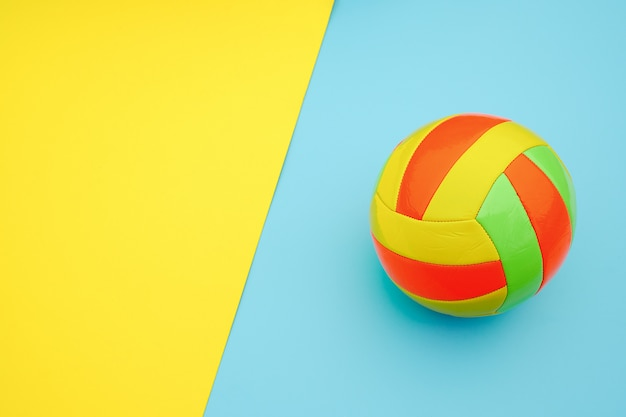 Bright multi-colored volleyball ball on yellow blue