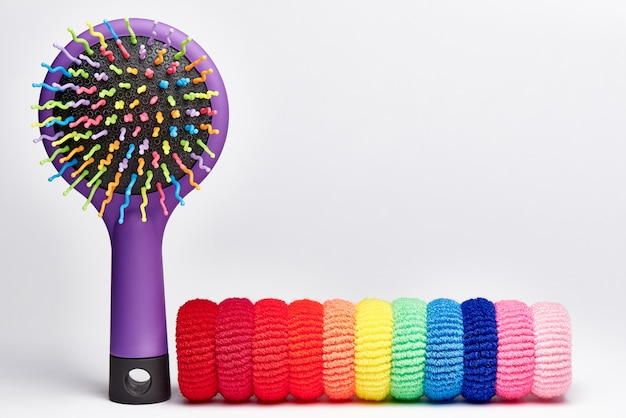 Bright multicolored hair brush with elastic bands for hair.