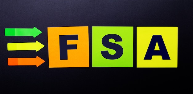 Яркие разноцветные бумажные наклейки на черной поверхности с текстом fsa flexible spending account.