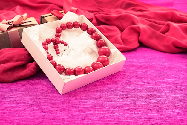 Bright necklace is packed in a white box on a pink background.