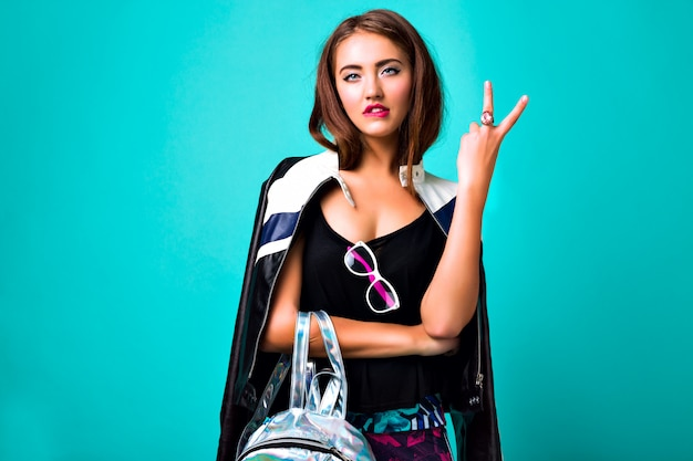 Bright neon fashion portrait of cheeky beautiful trendy woman, bright clothes and accessorizes, hipster style, leather jacket, backpack, young model