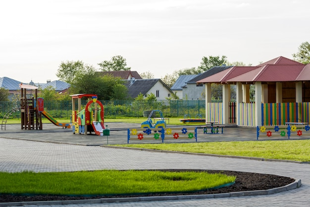 Яркий новый альков с красной черепичной крышей и разноцветным низким забором на зеленой лужайке в детском саду. идеальное место для веселых игр, отдыха и развлечений, построенное с любовью и заботой.