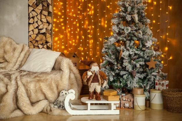 밝은 새해 축하 장식. 크리스마스 인테리어가있는 라이트 룸, 반짝이는 화환과 공으로 장식 된 크리스마스 트리