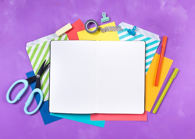 Bright office supplies, school stationery, white notepad on the table, purple background. back to school concept. top view. copy space.