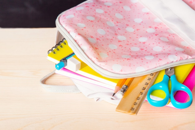 Bright open school bag with school supplies lies on a desk against the background of a school blackboard