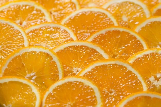 ジューシーなオレンジのスライスから明るいオレンジ色の背景。健康食品、背景。