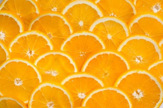 ジューシーなオレンジのスライスから明るいオレンジ色の背景