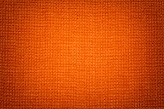 Bright orange background from a textile material with wicker pattern, closeup.