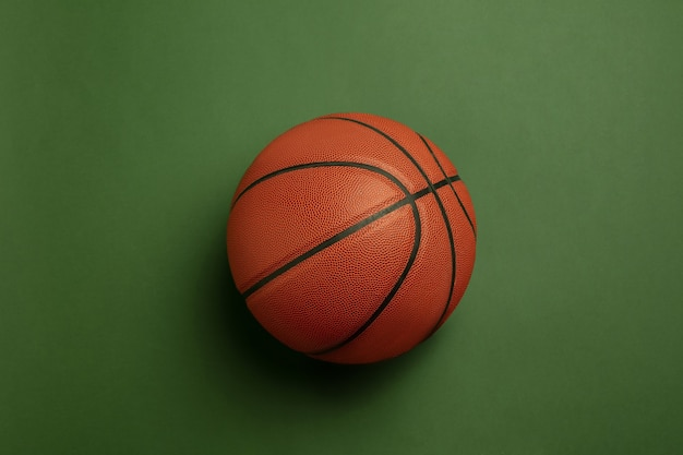 Bright orange-braun basketball ball. professional sport equipment isolated on green background.