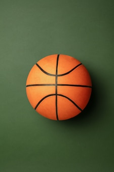 Bright orange-braun basketball ball. professional sport equipment isolated on green studio background. concept of sport, activity, movement, healthy lifestyle, wellbeing. modern colors.