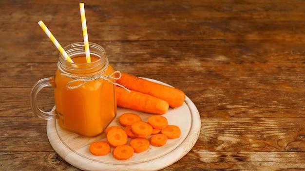 나무 배경에 유리 항아리에 밝은 오렌지 당근 주스. 주스와 다진 당근. 비타민이 함유된 수제 음료