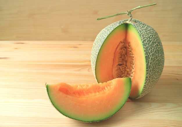 Bright orange color juicy ripe cantaloupe melon sliced from whole fruit on wooden table
