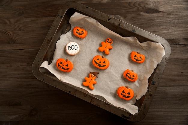 Ярко-оранжевое печенье в виде тыкв и забавных человечков лежит в форме для запекания. вкусное имбирное печенье. хэллоуин
