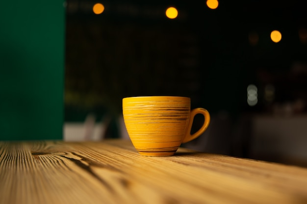 Ярко-оранжевая чашка на размытом темном фоне с боке