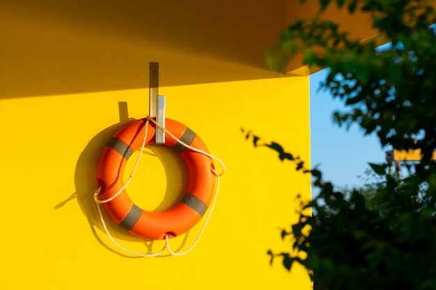 A bright orange life ring hanged against on bright yellow concrete wall