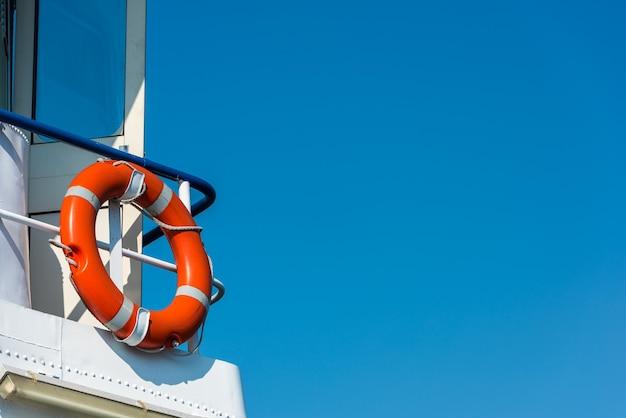 흰색 요트 측면에 밝은 주황색 구명 부표. 푸른 하늘 배경