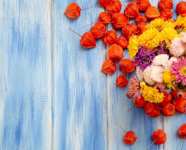 Ярко-оранжевые ягоды физалиса и осенние цветы на голубом древесном фоне