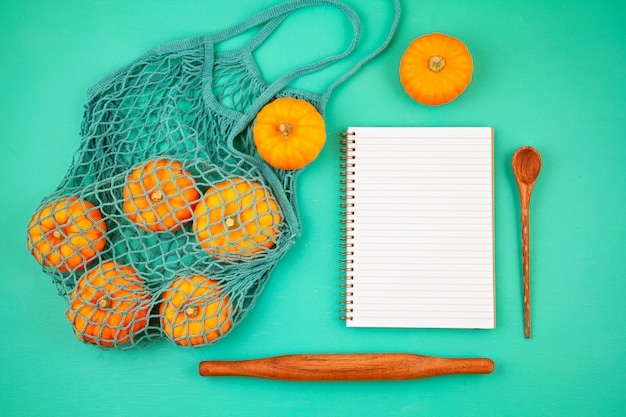 Bright orange pumpkins in mesh bag and empty notepad for shopping list or recipe