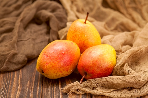 Bright orange ripe pears on a wooden brown